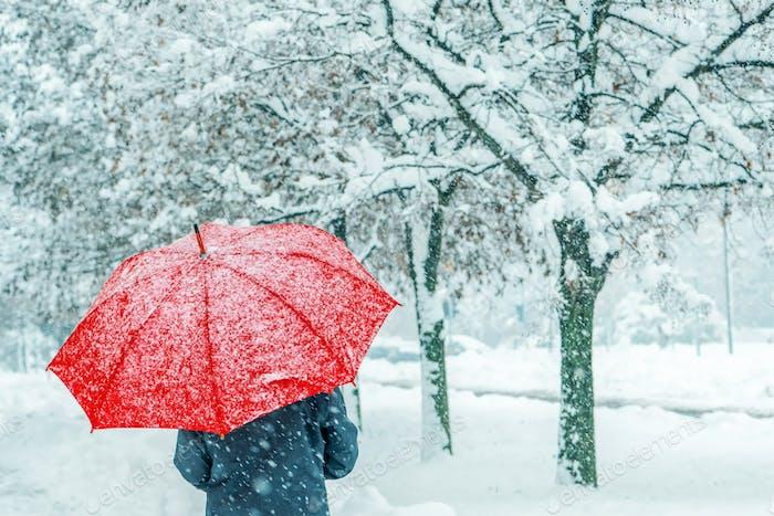 Mujer bajo paraguas rojo caminando en la nieve de invierno