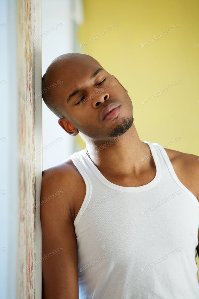 Man leaning against wall with eyes closed