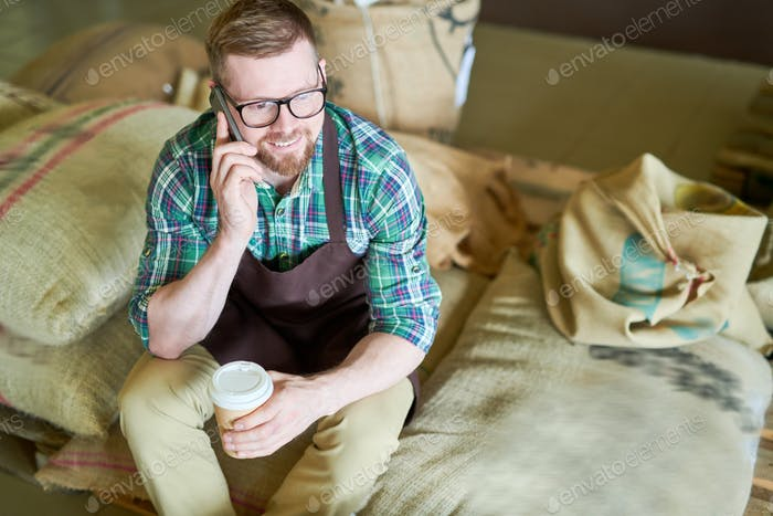 Barista Sitting on Bags with Coffee