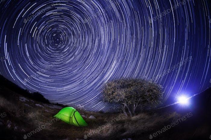 Grünes Zelt unter einem Baum gegen den Nachthimmel