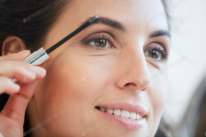 Woman Fixing Eyebrows With Gel