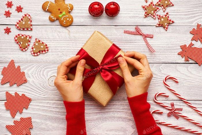 Weibliche Hände auf Weihnachtsgeschenk