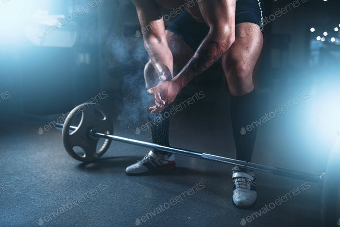 Athlete hands in powder and talc, barbell exercise