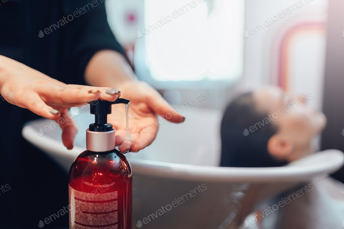 Hairdresser washes customer hair with shampoo