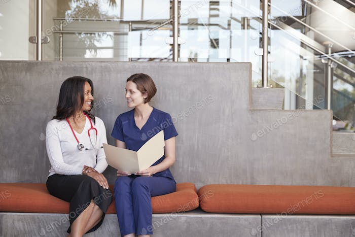 Two female healthcare workers discussing a medical record