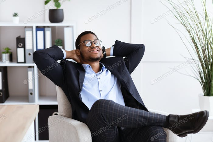 Young african businessman in formalwear relaxing at workplace