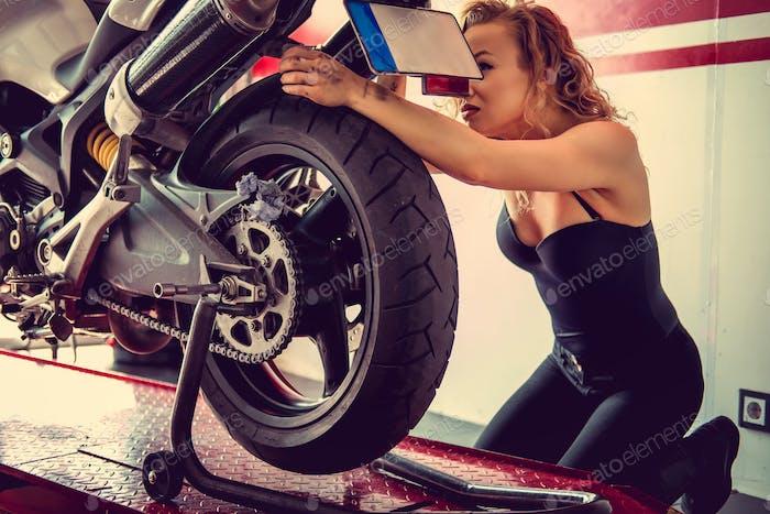 Sexy blond female repairing motorbcycle.