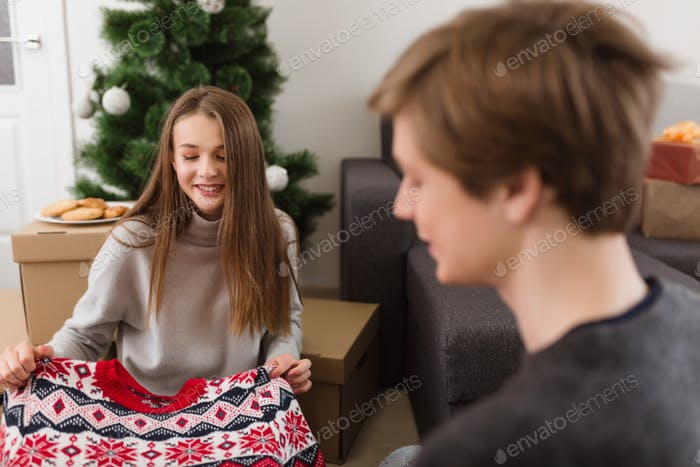 Pretty smiling girl holding new sweater sitting on floor at home near Christmas tree