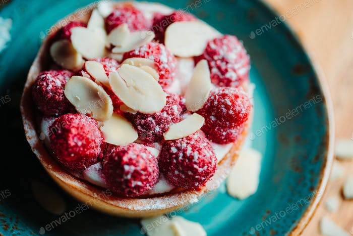Raspberry tartlet dessert with almond flakes