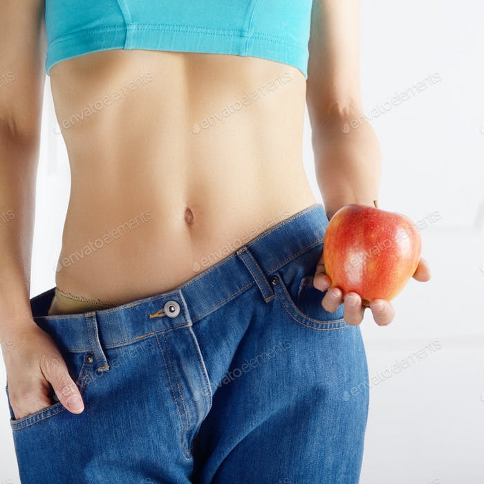 Caucasian female model in blue jeans with red apple showing her