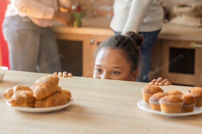 Kleines Mädchen mit Lust auf Süßigkeiten in Küche suchen