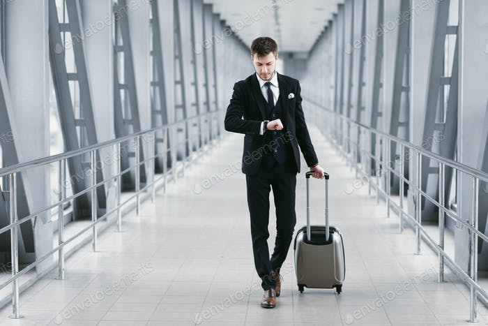 Adult business man standing in airport with suitcase