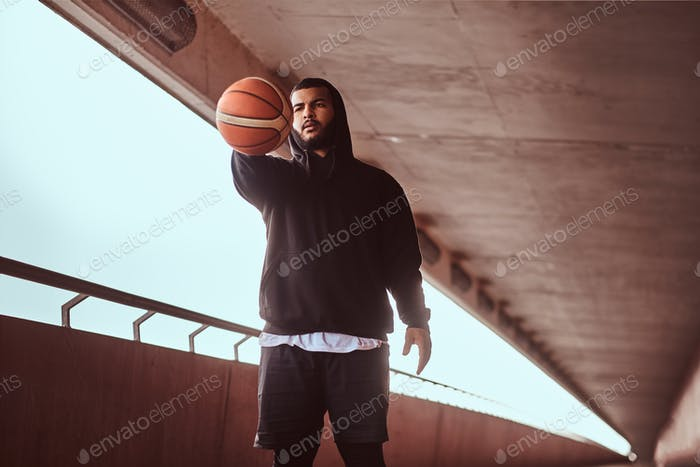 Темно-кожный парень держит баскетбол, стоя на пешеходной трое под мостом.