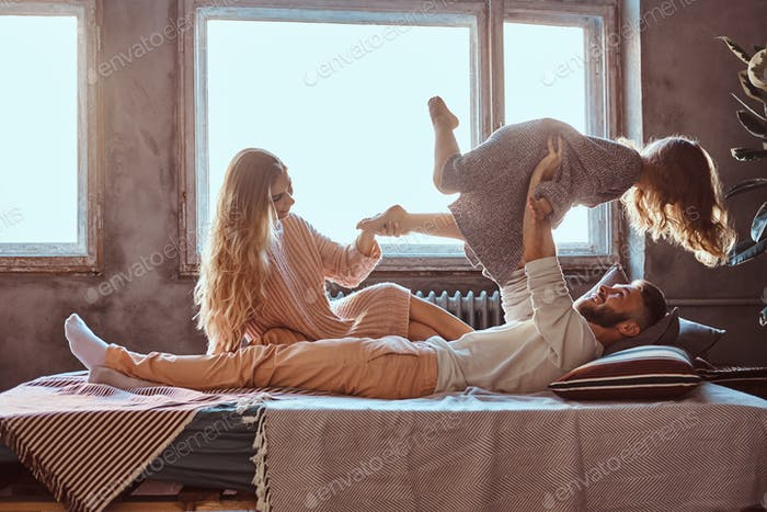 Mom, dad and daughter in bed. Father playing with adorable daughter in bedroom.