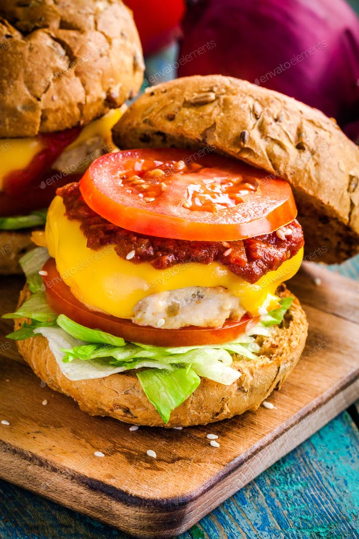 homemade burger with fresh vegetables, barbecue sauce and chicken cutlet