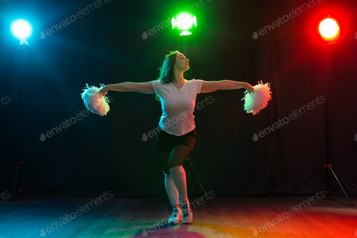 Full length portrait of cheerleader dancing with pom-poms