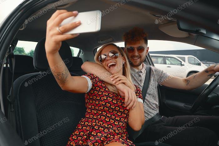 Glückliches Paar nimmt Selfie im Auto