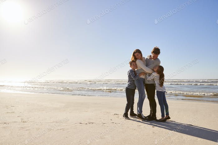 Loving Family Embracing On Winter Beach