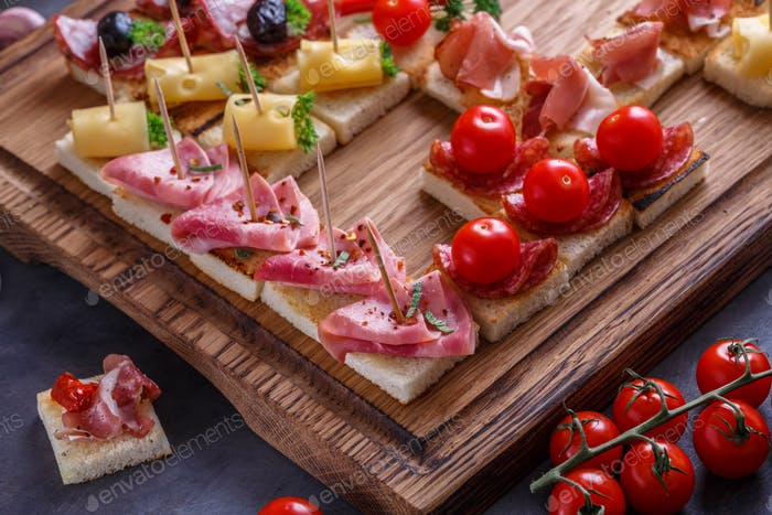 Jamon, ham, sausage and cheese on crusty garlicy bread or pinxtos, spanish cuisine
