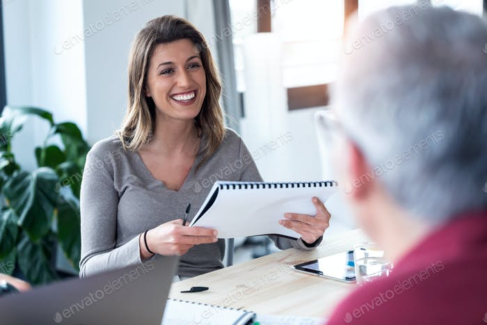 Smiling young business woman listening her partner while holding notes on coworking space.