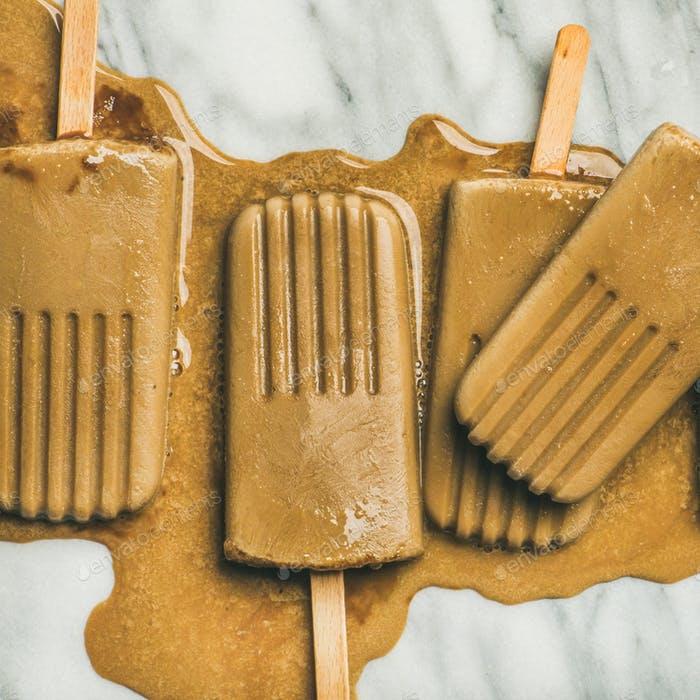 Flatlay of melting coffee latte popsicles on grey marble background