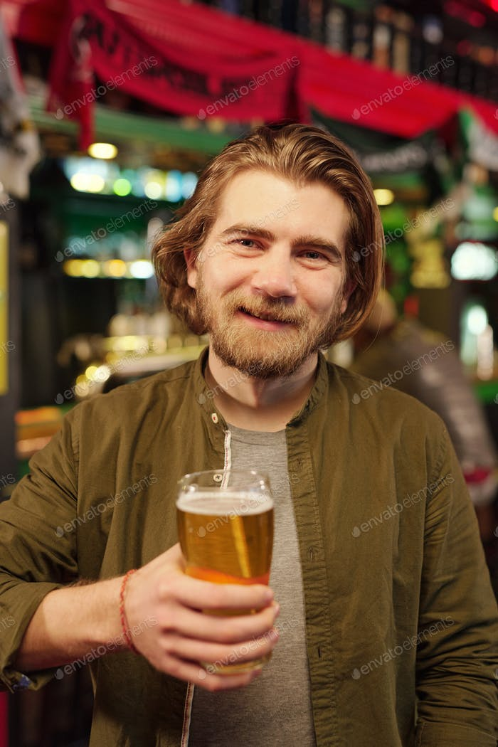Young cheerful bearded man looking at you with smile while toasting with beer