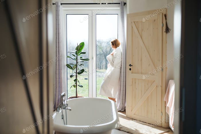 A young woman with bath robe standing in a bathroom by a window in the morning.
