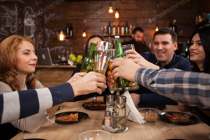 Group of happy friends drinking and toasting beer at brewery bar restaurant