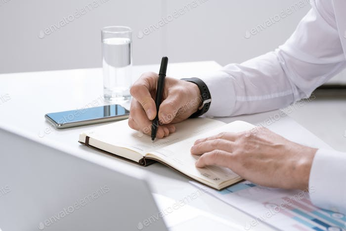 Hands of busy contemporary entrepreneur with pen over page of notebook