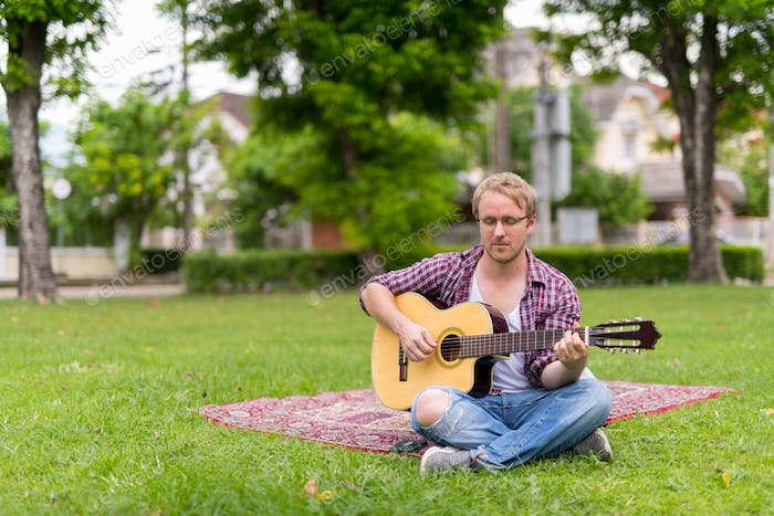 Portrait of man having picnic while playing the guitar outdoors