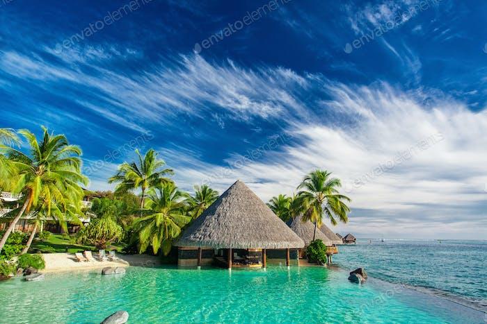 Infinity-Pool mit künstlichem Strand und Bar neben tropischem Oce