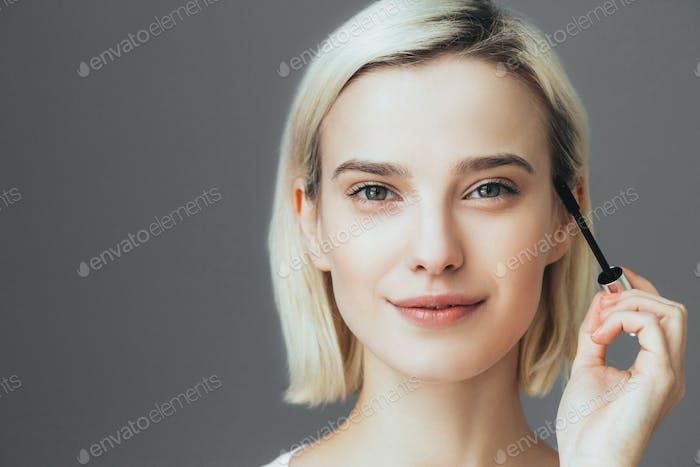 Woman mascara applying brush, female portrait makeup eyelashes.
