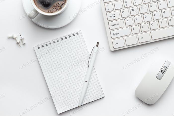 Bürotisch mit Notizblock, Computer und Kaffeetasse