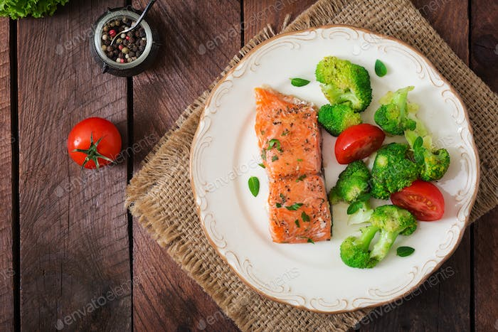 Baked fish salmon garnished with broccoli and tomato.