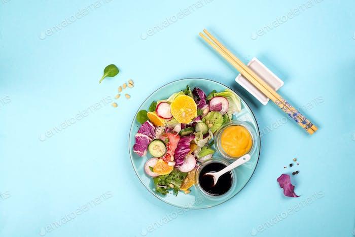 Frischer Salat mit Früchten und Grüns auf blauem Hintergrund