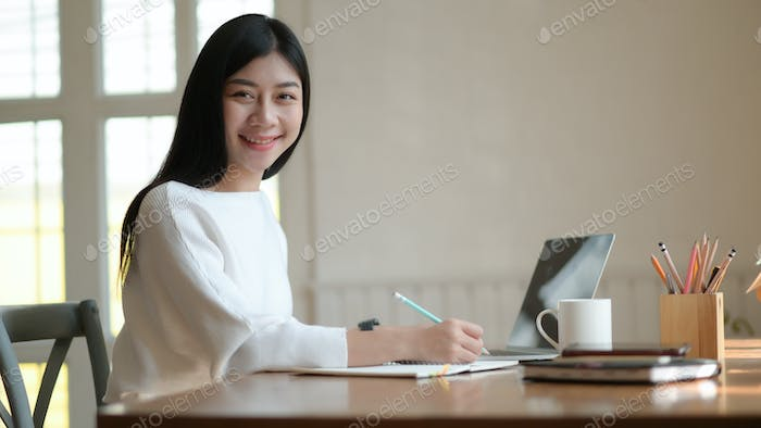 Young female student take notes and use laptop to search for research to prepare for graduation.