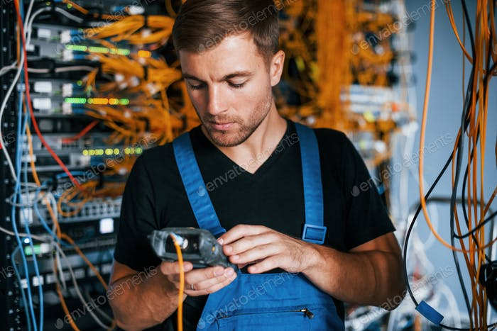 Young man in uniform have a job with internet equipment and wires in server room