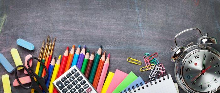 Schulbedarf auf Tafelhintergrund