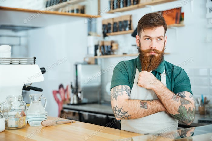 Handsome pensive man barista touching his beard and thinking