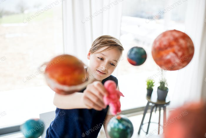 A small boy with model of solar system indoors