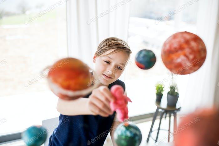 Ein kleiner Junge mit Modell des Sonnensystems drinnen