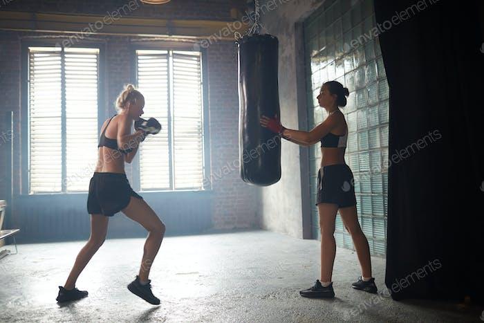 Tough Woman Hitting Punching Bag