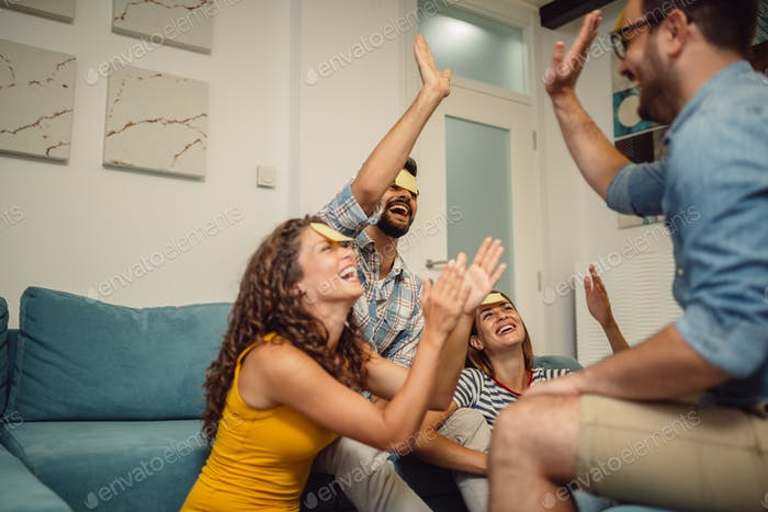 Portrait of happy friends playing game guess who and having fun at home