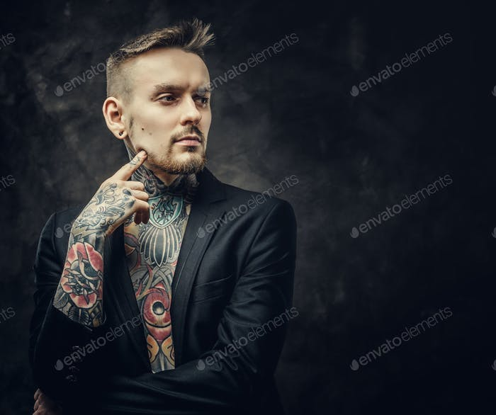 Confident and inked tattoo artist male model posing in a dark studio