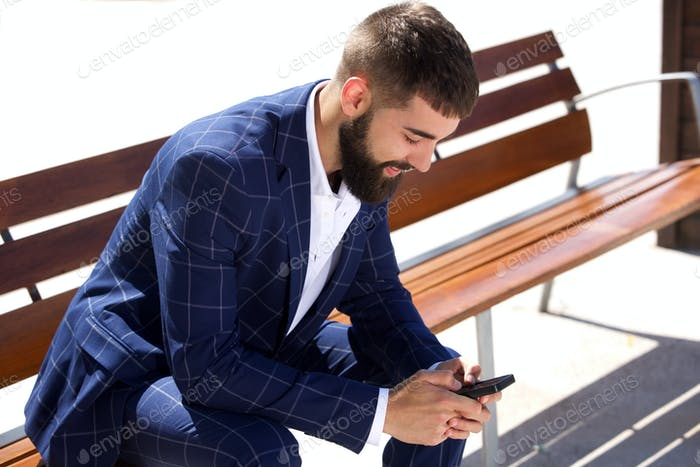 Businessman sitting on bench with mobile phone