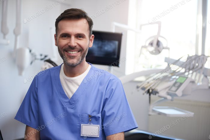 Portrait of smiling dentist in dentist's office