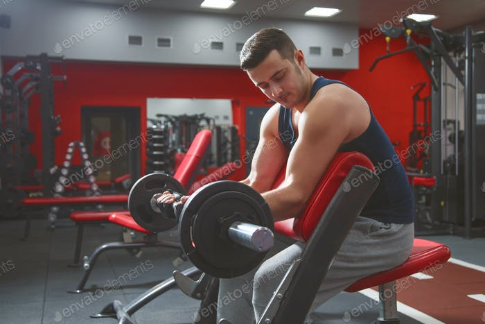 Thumbnail for Man doing biceps lifting barbell on bench in a gym