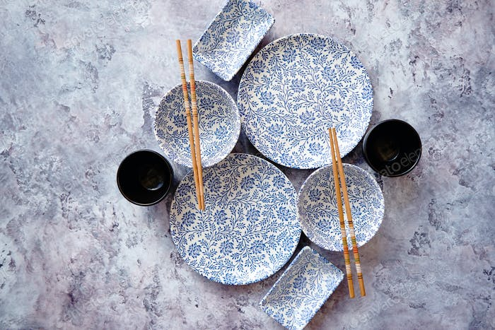 Empty oriental style dishware set on gray stone background