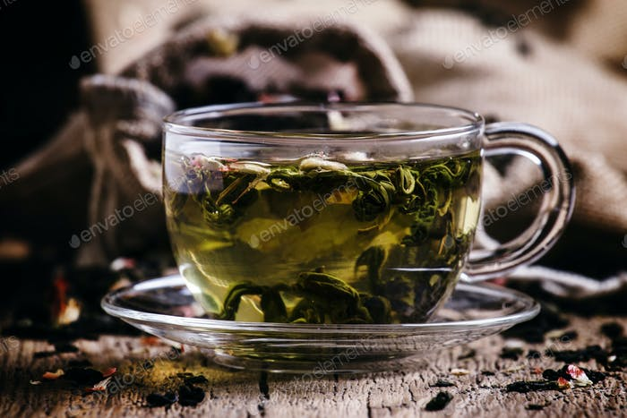 Cup of green tea with flower petals