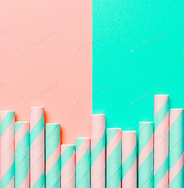 Gestreifte Papierstrohhalme auf rosa und blauen Hintergrund